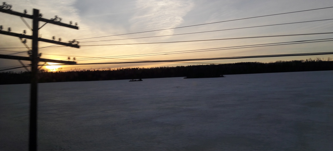 A sunset over an ice-covered lake, black firs in the background and telegraph wires in the foreground.