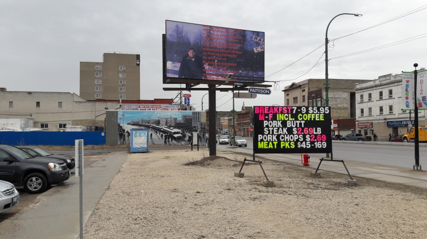 "Signs outside Neechi Commons workers' co-op in downtown Winnipeg, with dirt lots and buildings surrounding it. Adverts right and left; central, and artwork with a picture of a human figure and the text: ""niidaachag dahapii sinahae / niiya ngiigimoodiimiigo / my body was kidnapped / my spirit lives on"""