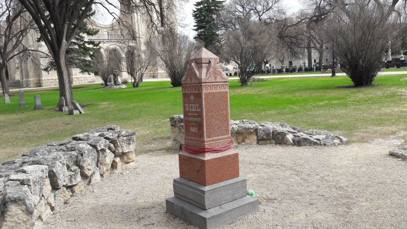 Louis Riel's grave, with a Métis sash wrapped around the column. A low wall surrounds it, and a half-destroyed cathedral is in the background, with a green lawn between.