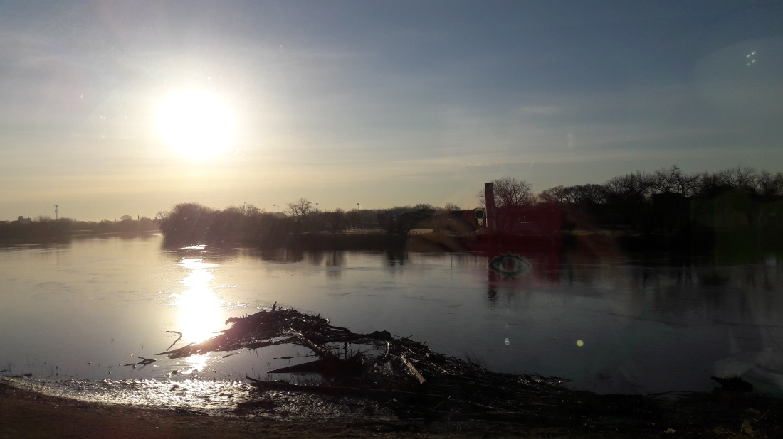 Sunrise over the Red River: a wide river on low prarie, fringed by trees yet to get spring leaf. Industrial buildings in the background, logs and branches in the foreground. The shadow of me in the window.