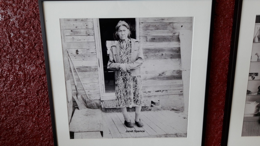 Janet Spence, a late middle aged woman standing in the door of her wooden house. She is wearing a print patterned dress and a short coatel and broom lean in the left of the picture. Her hands are clasped. The photo is labelled at the bottom. The photographer was not labelled in the gallery.