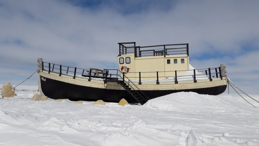 A little black and gold fishing boat, with steps leading up to it and a bench on top, moored and banked in by snow. You can't tell from the picture, but it was built in Buckie!