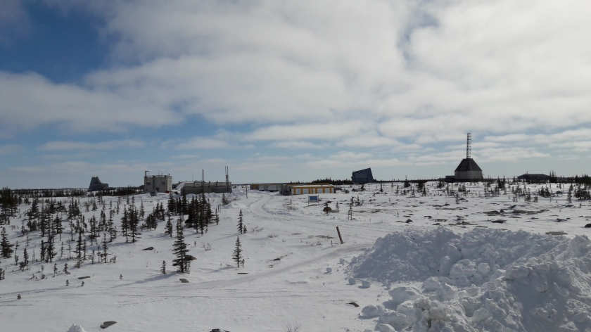 Blue sky and white clouds above, snow drifts and sparse boreal forest below. In between, an old rocket range: blocky huts of different shapes, one with a metal gantry pointing to the sky.