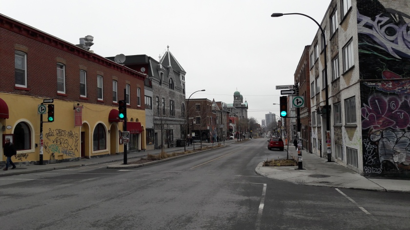 "A Montréal street scene with a mixture of new and old architecture, with graffiti and street art visible on the walls and a church far up the street. In the foreground a sign reads ""Rue Coloniale""."