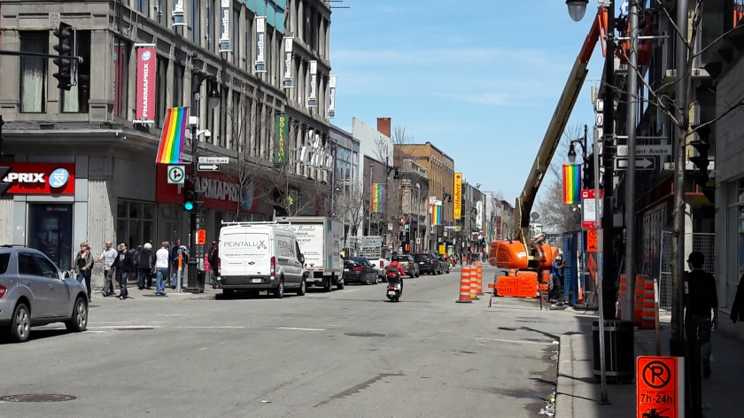 Le Village Gai, Montréal. There are igh street shops and a lot of condo construction; along the street, rainbow flags are visible. In the distance, things get pleasantly seedier.