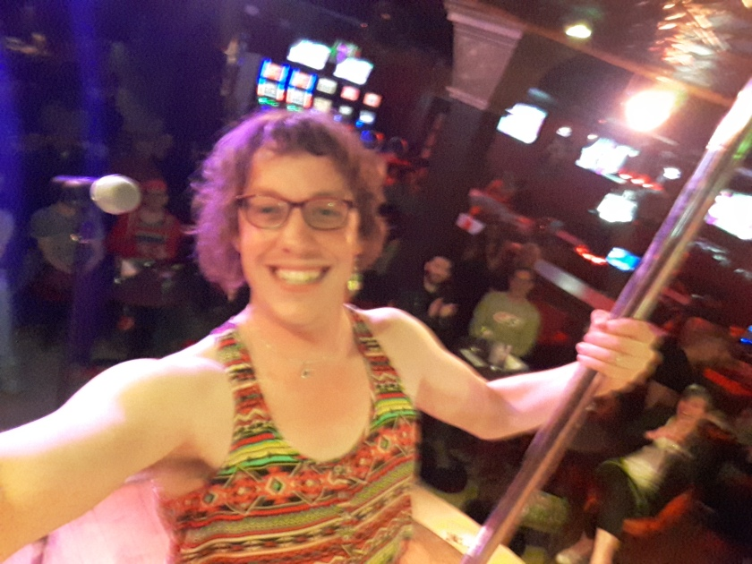 Your correspondent, on stage at the Stock Bar, with a crowd and glowing lights behind. I'm wearing a brightly-patterned strappy top, pink glasses, bouffant hair, and am leaning away from a metal pole.